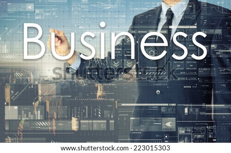 the businessman is writing Business on the transparent board with some diagrams and infocharts with the city in the background - stock photo