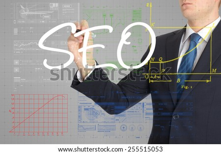 the businessman is writing SEO on the transparent board with some diagrams and infocharts - stock photo