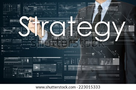the businessman is writing Strategy on the transparent board with some diagrams and infocharts with the dark elegant background - stock photo