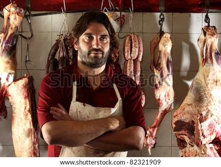 the butcher of the neighborhood in his shop - stock photo