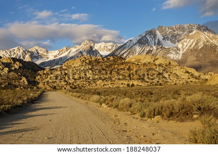 the Buttermilk dirt road heads towards the mountains of the Eastern Sierra Nevada in California early in the morning - stock photo