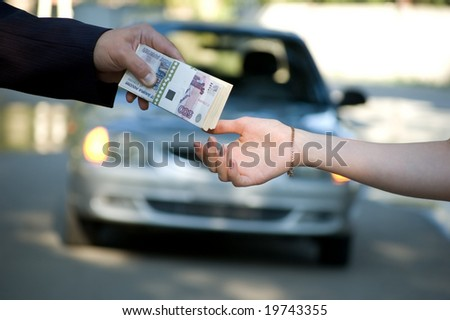 The buyer transfers money for the new car - stock photo
