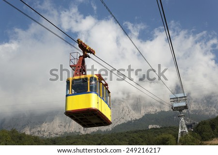 The cable car in Crimea Ai-Petri on a background of mountains covered with clouds - stock photo