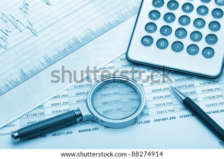 The calculator,loupe and the financial report blue tone. A workplace of the businessman - stock photo