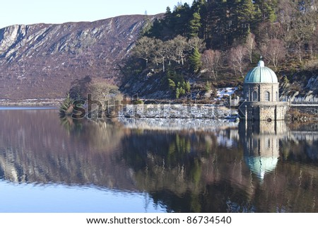 the calm waters of a reservoir at elan valley - stock photo