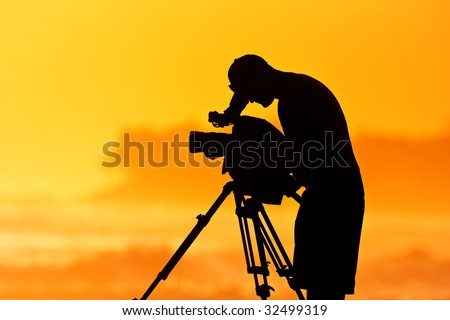 The Cameraman, Silhouette of Man with Video Camera at Sunset - stock photo