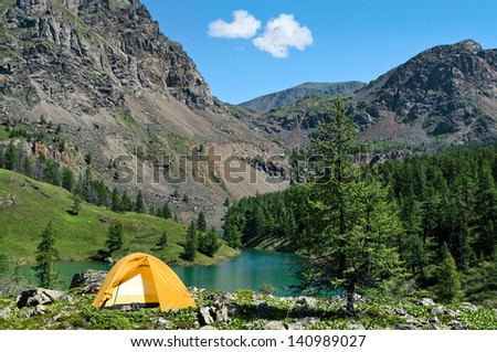 The Camping Tent near mountain lake in the summer - stock photo