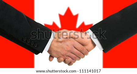 The Canadian flag and business handshake - stock photo