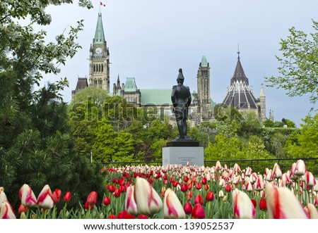 The Canadian Parliament Centre Block and Library with the statue of Colonel John By  during spring with many red and white tulips. - stock photo