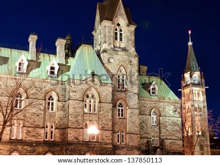 The Canadian Parliament West Block and Clock Tower in Ottawa at dusk. - stock photo