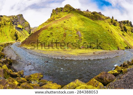The canyon Pakgil is located among fantastic rocks. On a bottom of a canyon  fast shallow stream flows. The summer blossoming Iceland. The photo was taken Fisheye lens - stock photo