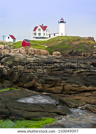 The Cape Neddick seacoast near York, Maine is home to the Nubble Light, a lighthouse perched upon a small rocky island. - stock photo