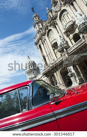 The Capitolio Building stands behind a view of the landmark architecture of the Great Theater of Havana with a bright red accent of vintage American car - stock photo