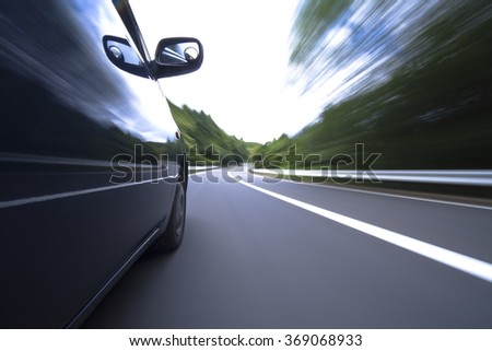 The car moves at great speed at the mountain road  - stock photo