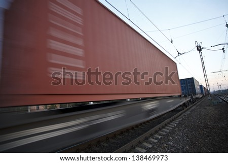 The cargo train moving at great speed by station - stock photo