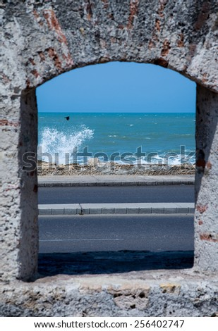 The Caribbean Ocean kicks up waves and a bird flies by as seen through the ramparts of the old city wall around Cartagena. - stock photo