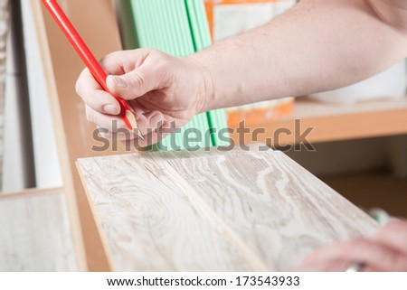 The Carpenter is drawing a line on the laminate. - stock photo