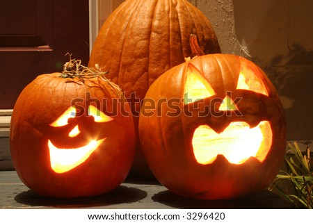 The carved faces of pumpkins glowing on Halloween. - stock photo