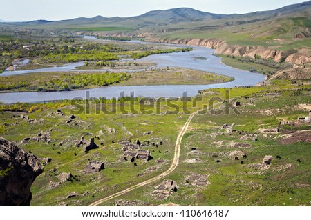 The Caucasus with the pasture, the river and the remains of the destroyed ancient archeological structures - stock photo