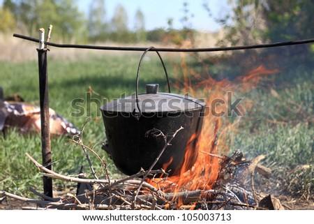 The cauldron hanging above bonfire on picnic - stock photo