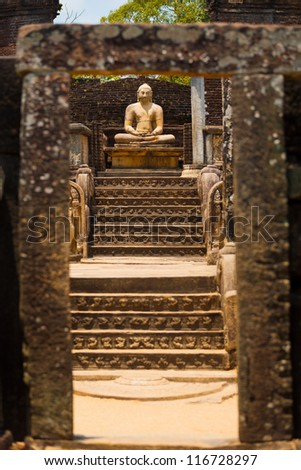 The central stone Buddha statue and steps of the Vatadage are framed by a stone gate at the ancient kingdom capitol of Polonnaruwa, Sri Lanka - stock photo