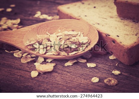 the cereal and black sesame bread with whole grain cereal flakes which mixed warming cinnamon , red skin apple , golden raisins and roasted hazelnuts on wooden plate - stock photo