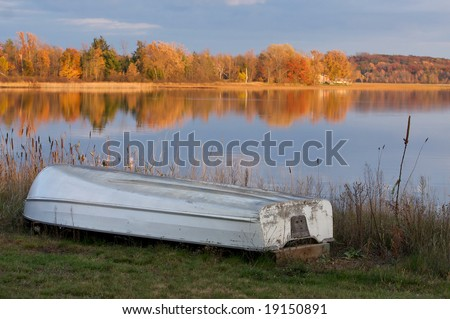 The change of seasons.  The boat is out of the water and the leaves are changing - stock photo