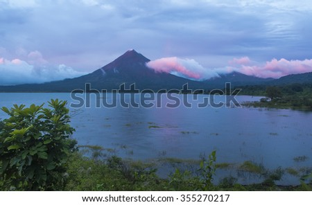 The changing colors of the clouds during a sunset on Arenal Volcano - stock photo