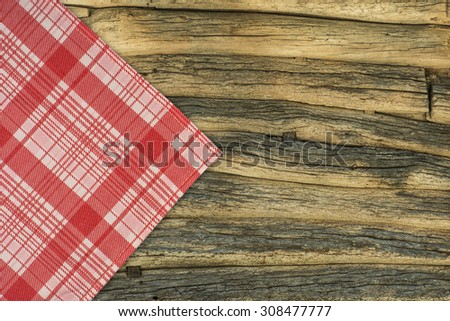 the checkered tablecloth on wooden table - stock photo