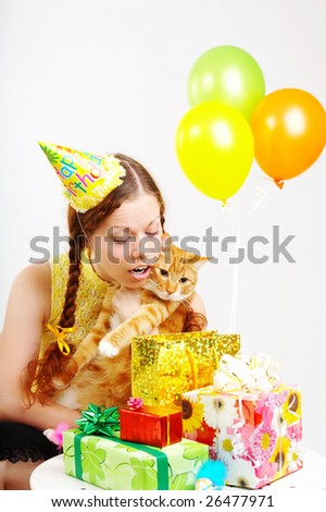The cheerful birthday woman considers gifts with a cat in hands - stock photo