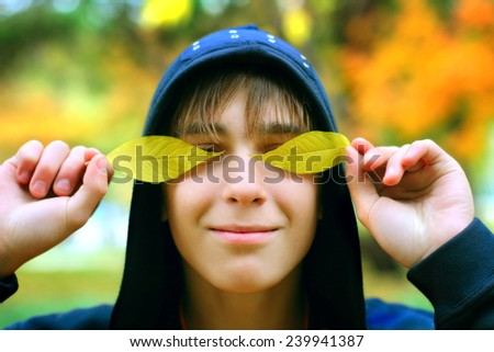 The cheerful teenager in autumn park - stock photo
