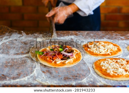 The chef is going to put the pizza in oven. Close up. - stock photo