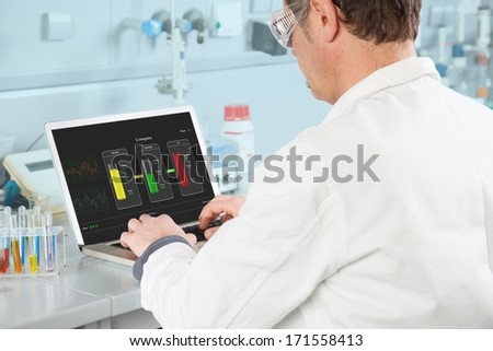 The Chemist is examining the Test Result on his PC. - stock photo