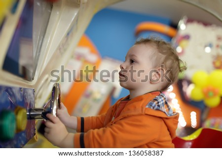 The child and amusement car at indoor playground - stock photo