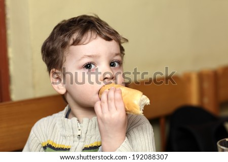 The child eating bun in the cafe - stock photo