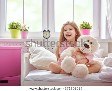 The child girl woke up and enjoys the morning sun. Girl laugh and hugs the teddy bear. - stock photo