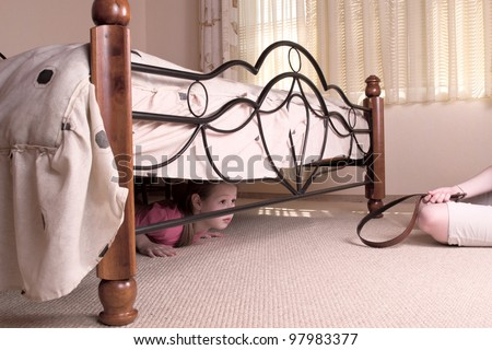 The child hides under a bed. Violence in a family. - stock photo