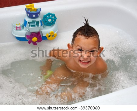 The child in bathing filled with water with foam - stock photo