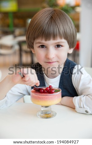 the child in the cafe with berry mousse - stock photo