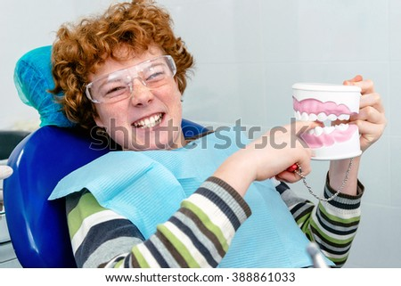 The child in the dental chair, playing with teeth layout - stock photo