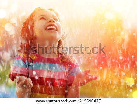 the child is happy with the rain - stock photo