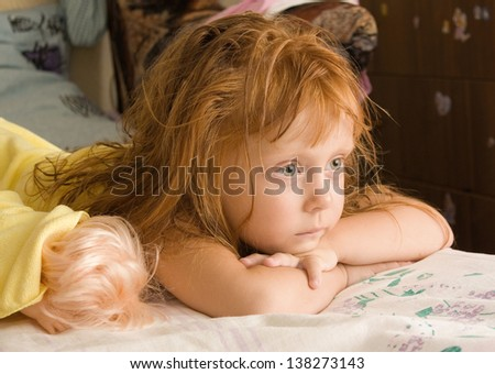 The child is lying on the bed - stock photo