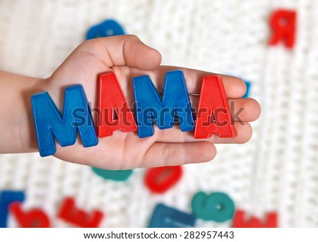 """The child is of colored letters on the palm of the word """"mother"""" - stock photo"""