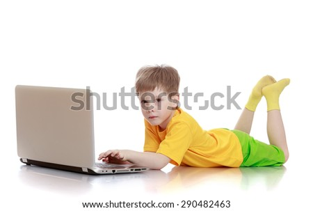 The child lies on the floor and looks at the laptop screen - isolated on white background - stock photo