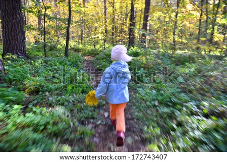 The child runs through the forest with special motion blur effect  - stock photo