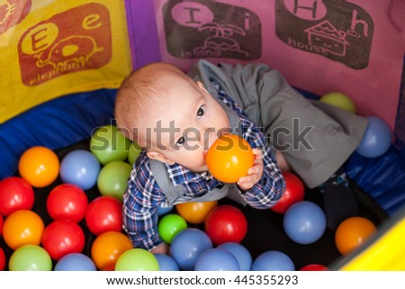 The child sits in the game room in the arena with colorful balls and chewing on them, because he is teething or hungry - stock photo