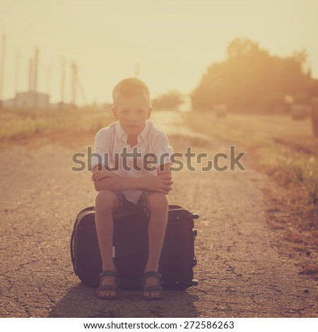 the child sits on a suitcase in the summer sunny day, the traveler. Toned image - stock photo