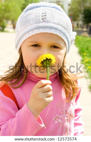 The child smells a yellow dandelion - stock photo