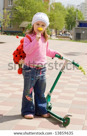 The child with a skateboard, smells a flower - stock photo
