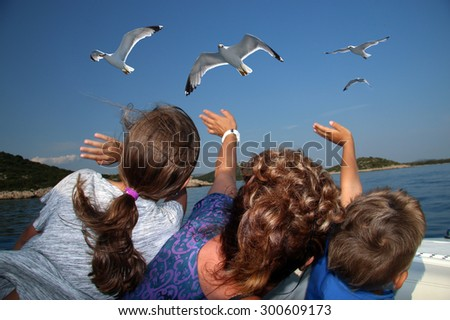 The children are feeding and waving the seagull on the boat - stock photo